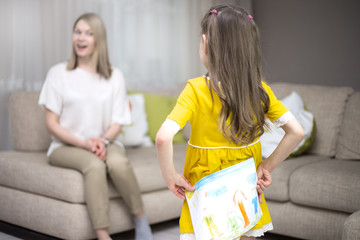 Child daughter congratulates mom and gives her painting. Mum and girl smiling and hugging.