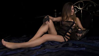 Gorgeous girl lies waiting on the black satin lingerie