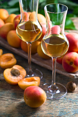Juicy apricots with leaves and glass of sweet wine .
