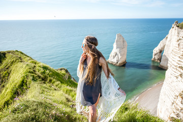 Young woman dressed in hippie style enjoying nature on the rocky coastline with great view on the ocean in France