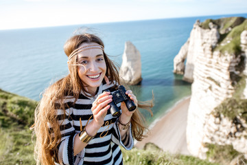Young woman watching with binoculars on the famous rocky coastline near Etretat town in France
