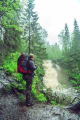 Hiker with a backpack near waterfall.