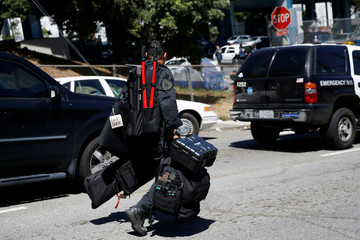 A police officer carrying equipment walks towards a UPS facility after a gunman opened fire inside the building in San Francisco