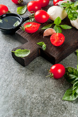 Farm raw organic products. Preparation of dinner in the Italian style. Ingredients for caprese salad, pasta, pizza. Basil, tomatoes, mozzarella cheese, olive oil on dark grey stone table. Copy space