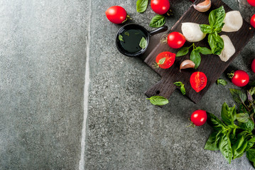 Farm raw organic products. Cooking of dinner in Italian style. Ingredients for caprese salad, pasta, pizza. Basil, tomatoes, mozzarella cheese, olive oil. dark grey stone table. Copy space top view