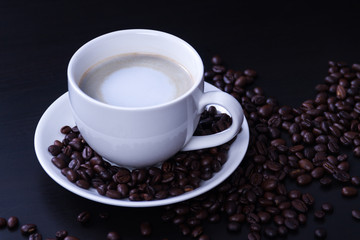 Hot coffee in the white cup and roasted on dark background