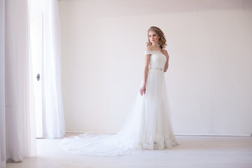 bride in wedding dress in a white room