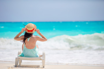 Back view of girl in hat on a tropical beach looking on the beautiful sea