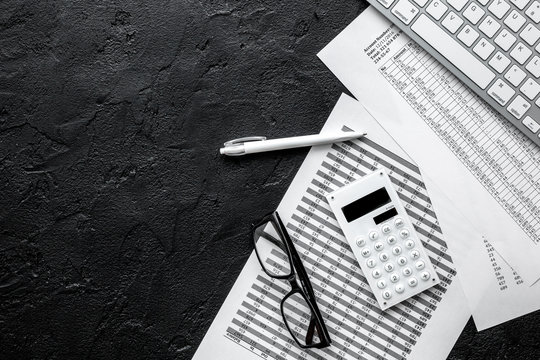accounting work space with calculator, profit and tables on dark desk top view mock-up