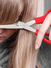 Woman cutting her fringe.