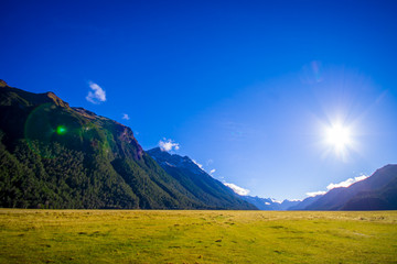 Beautiful landscape of high mountain glacier at milford sound with a sunshine in the sky, in south island in New Zealand