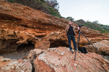 Young male photographer standing on rocks with tripod and making photos of sea
