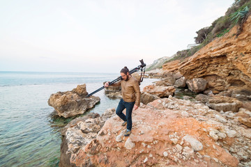 Young male photographer walking on rock beach with camera on tripod