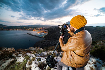 Young attractive photographer making photos with camera on tripod at sunset