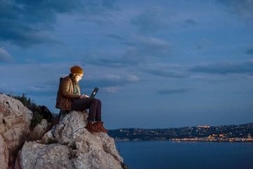 Young attractive photographer sitting on rock and working on laptop with view of sea and mountains