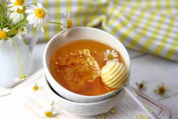 мед в сотах в керамической миске с ромашкой