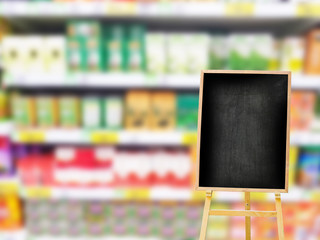 empty or blank menu black board on the right on blurred colorful products on the shelf in supermarket