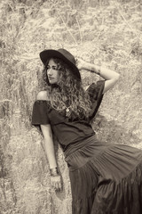 beautiful woman in black dress and hat posing at stone wall background