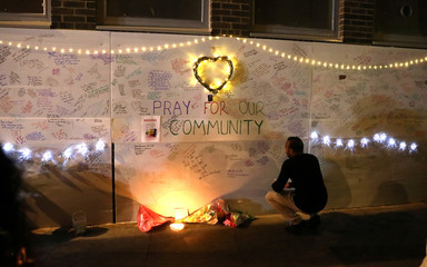 A man reads messages of condolence on a wall  near a tower block severely damaged by a serious fire, in north Kensington, West London