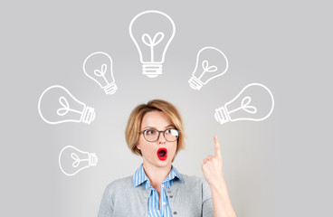 Beautiful business woman has an idea showing finger up on light bulb over her head. Brainstorm. Decision making concept
