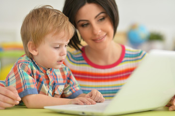 Mother and son using modern laptop