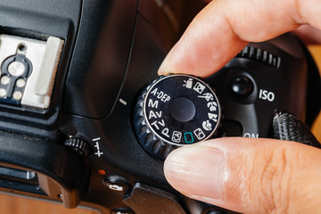 Manual dial mode on dslr camera with fingers on the dial