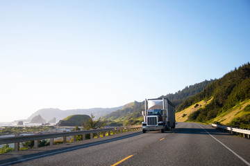Dark classic semi truck with trailer driving on highway along the Pacific coast in Northwest