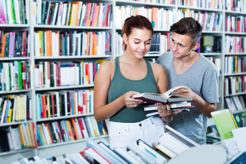 Two smiling teenagers reading book together
