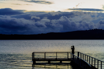 Silhouette young woman using mobile phone taking picture of beautiful Lake Taupo in the evening , North Island of New Zealand