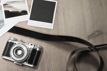 Retro vintage photography concept of three instant photo frames cards on wooden background with images of nature and blank black photo frame with old camera and film strip top view