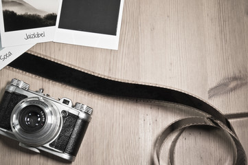 Retro vintage photography concept of three instant photo frames cards on wooden background with images of nature and text and blank black photo frame with old camera and film strip top view