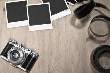 nostalgic concept blank instant photo frames on wooden background with old retro vintage camera with film strip and copy space
