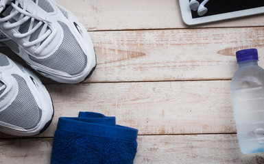 Sport shoes, mobile phone , towel and  water on wood background