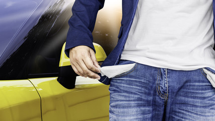 Man showing his empty pockets with yellow car background.