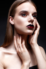 A young girl with long straight hair and bright evening makeup. Beautiful model with red lips. Pure shining skin. Beauty of the face.