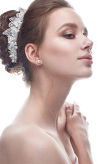 A young girl in a gentle wedding image with a diadem on her head. Beautiful model in the image of the bride on a white isolated background with nude makeup. Pure shining skin. Beauty of the face.