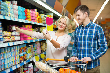 Young  family choosing dairy products and smiling