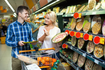 Young satisfied family couple choosing chilled pizza