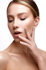 Young girl with perfect shining skin. A beautiful model with a foundation and nude makeup. Clean skin. White isolated background. Beauty of the face.
