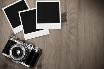 nostalgic travel memories from the past concept: still life three blank instant photo frames on old wooden background with old retro vintage camera with copy space