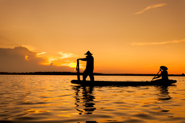 Silhouette,Two fishermen using nets for fishing,sun background