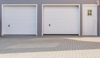 Doppelgarage mit weißen Toren und weißer Tür