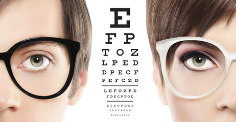 eyes and eyeglasses close up on visual test chart, eyesight and eye examination concept in white background