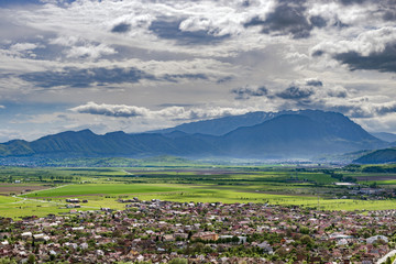Spring view over Rasnov city, in Brasov county (Romania), with Piatra Craiului mountains in the background. Picturesque medieval town viewed from above, with mountains landscape