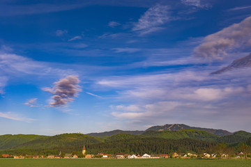 Beautiful sunset panorama over Cristian village (Brasov county, Romania) with the medieval ethnic german church in the left side and Postavaru mountains in the background