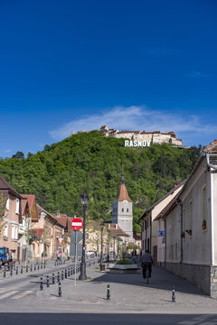 Rasnov, Romania - May, 2017: View of the Rasnov city mainstreet (Brasov county (Romania), with the hill of the medieval Rasnov fortress and city name in the Hollywood style