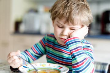 Adorable little school boy eating vegetable soup indoor.