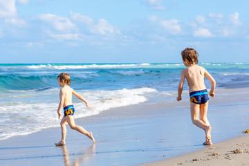 Two kid boys running on ocean beach in Florida