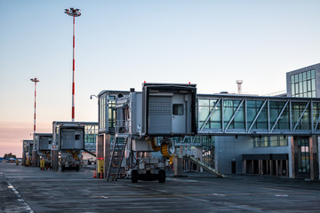 Empty passenger boarding bridges at the early morning airport apron