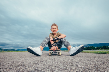 Boy sitting on skateboard on asphalt road
